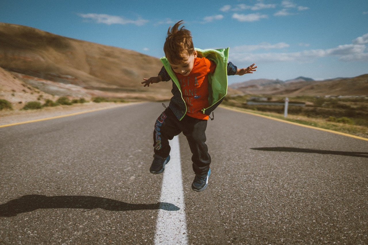 child jumping on a highway road