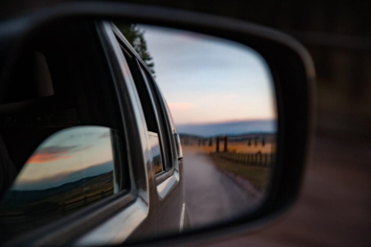 country road trip view from side view mirror