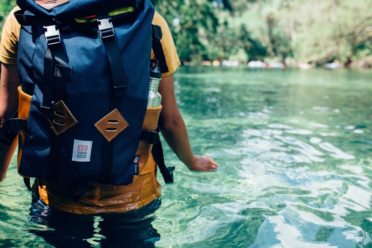 Walking through water with a packed hiking bag