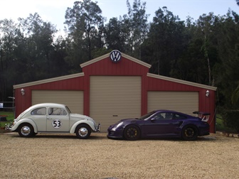 Two cars facing each other outside a garage