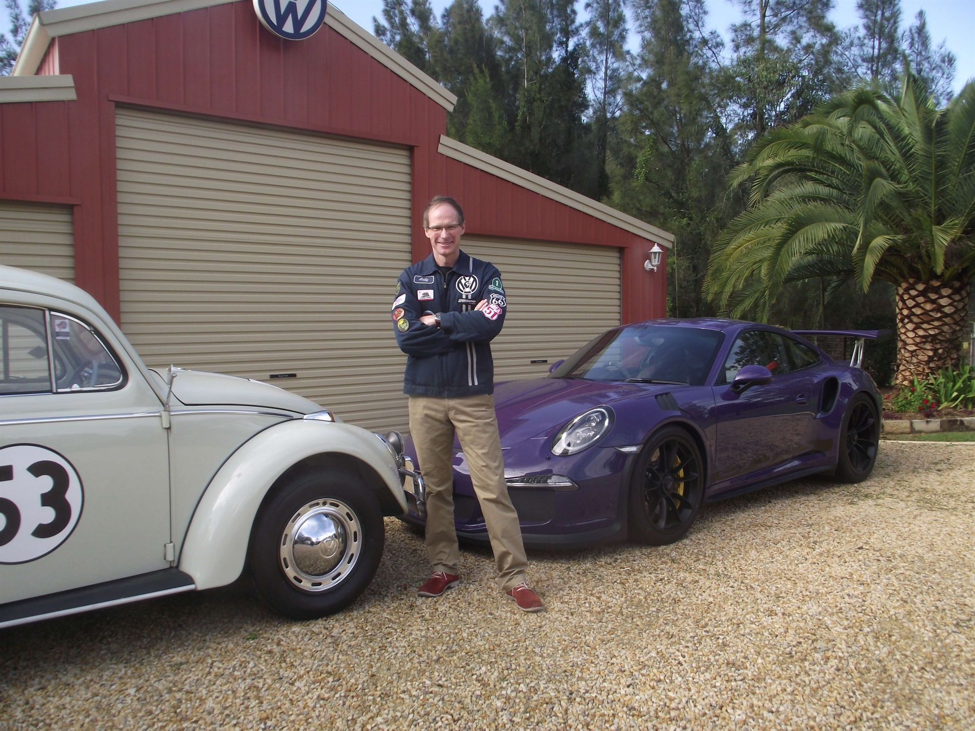Andy Roberts standing in front of two cars